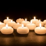 Several white candles on a black background